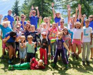International summer camp - group of kids and teachers jumping in the air