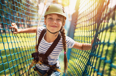 International summer camps - girl walking across a ropes course