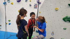 Altitude Camps Blog - two kids climbing with the assistance of an instructor