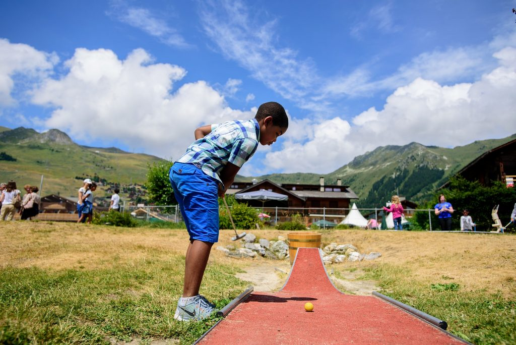 Sports camps - kid hitting a mini golf ball