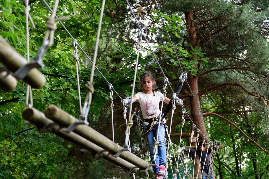 Residential camps - kids crossing bridge high in the trees