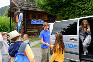 Preparing for camp - kids getting out a van being greeted by a team member