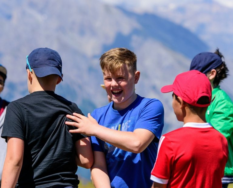 Switzerland summer camps - laughing boy up the mountain
