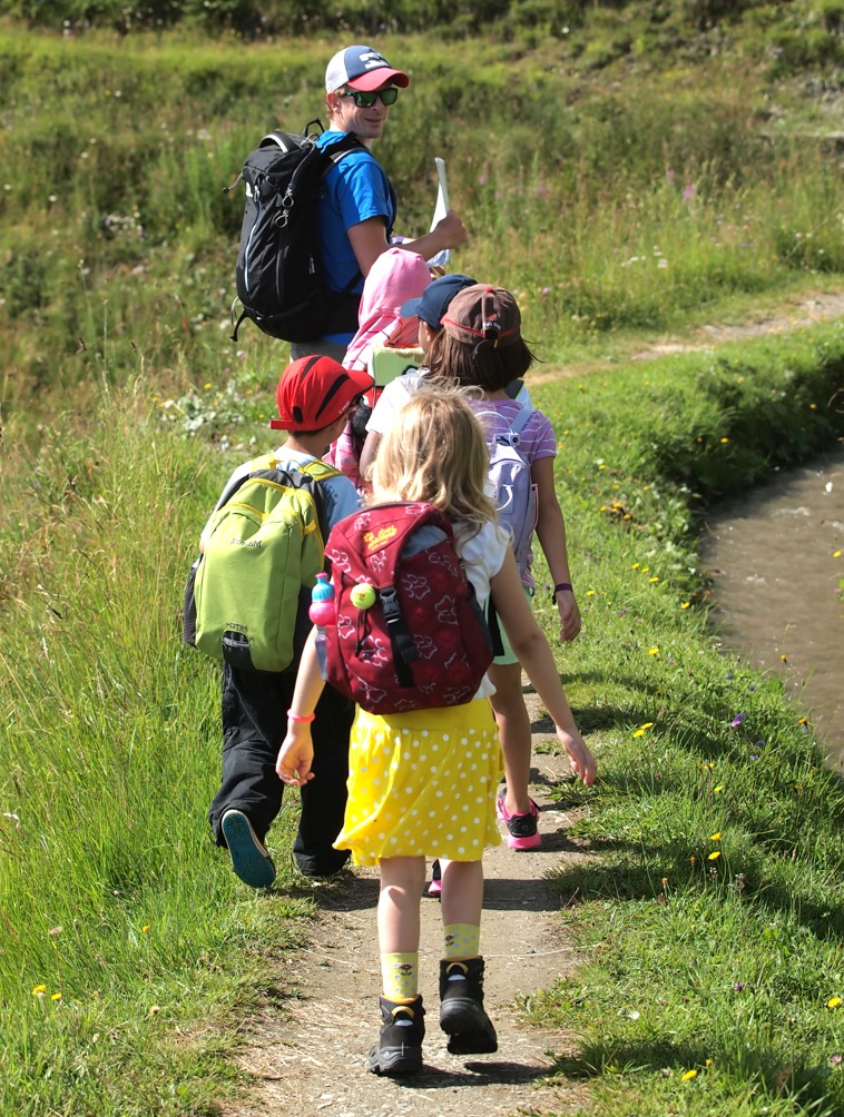Summer camps in Switzerland - group of kids hiking in the mountains